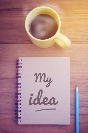 60837622 - cover page of notebook with word, my idea, and pencil and hot coffee on wood table, concept of start working on my plan in morning time, glow light effect, retro filter, vintage style.